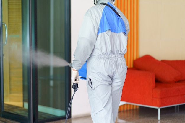 Persoon in beschermend pak desinfecteert het gebied