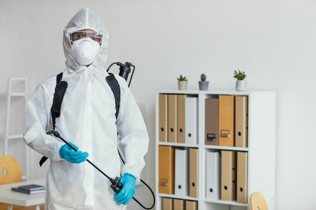 Persoon in beschermend pak die zich klaarmaakt om een kamer te desinfecteren