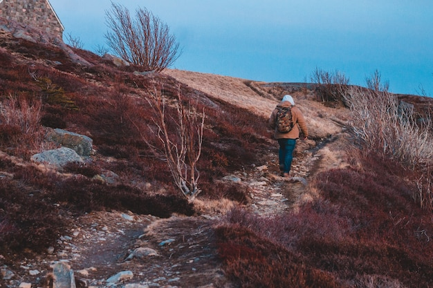 Persoon in bruine jas en zwarte broek staande op bruin grasveld overdag