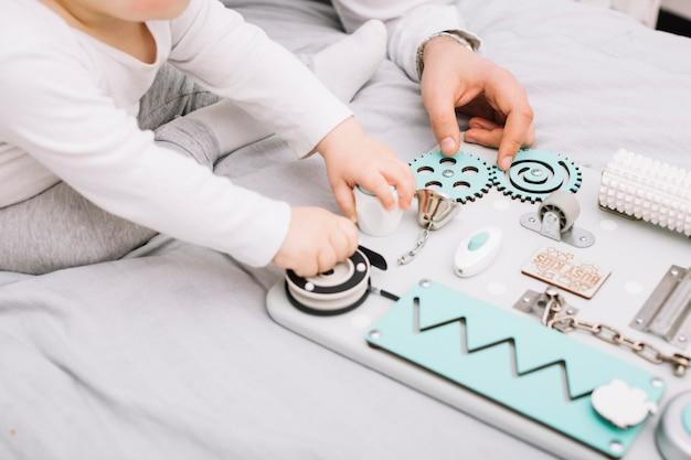 Persoon in de buurt van kleine baby met speelgoed zittend op bed