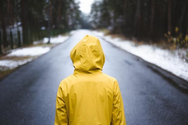 Persoon in de gele regenjas staat op de weg in het midden van het bos.