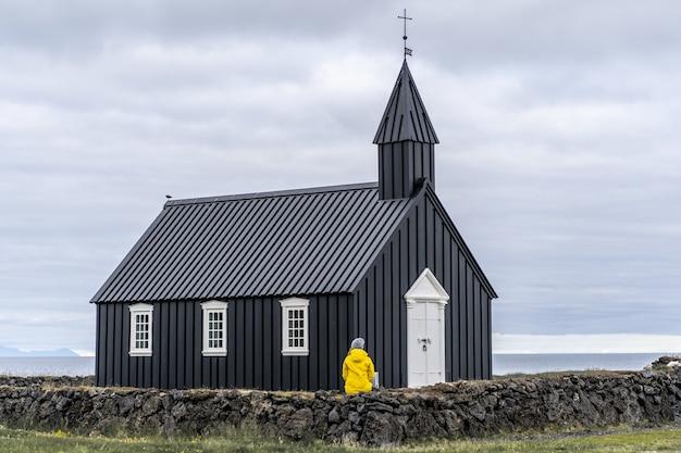 Persoon in een gele jas zittend op een kleine muur voor de buoir in ijsland