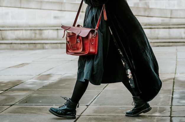 Persoon in een zwarte jas met een tas terwijl hij op straat loopt