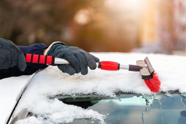 Persoon in handschoenen sneeuw vegen uit de auto in zonnige dag