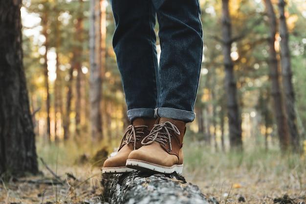 Persoon in laarzen en jeans op stam, ruimte voor tekst