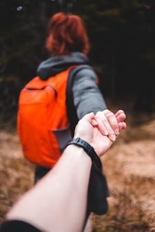 Persoon in oranje jas en zwarte horloge hand in hand met man in zwart shirt met lange mouwen