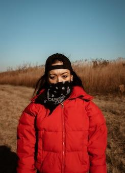 Persoon in rood jasje dat zwarte bandana draagt