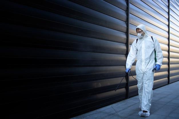Persoon in wit chemisch beschermingspak die desinfectie en ongediertebestrijding uitvoert en gif sproeit om insecten en knaagdieren te doden