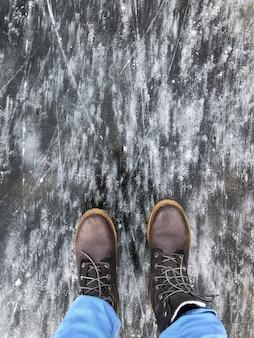 Persoon in zware laarzen die zich aan het oppervlak van het bevroren meer van methaanbellen bevinden