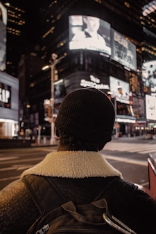 Persoon in zwarte gebreide muts en bruine jas die 's nachts op straat staat