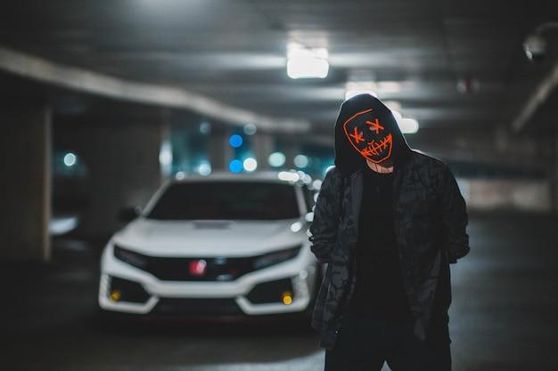 Persoon in zwarte hoodie met zwart en oranje masker