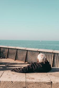 Persoon in zwarte jas zittend op bruin houten bankje in de buurt van zee overdag