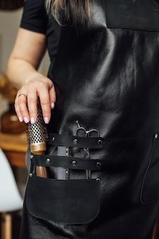 Persoon in zwarte schort met professionele kapper ingesteld op donkere achtergrond close-up