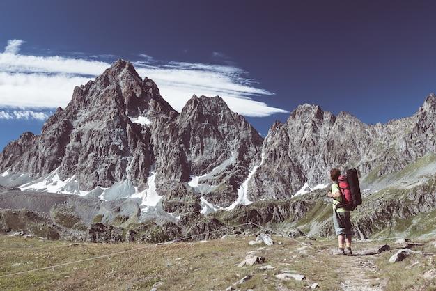 Persoon kijken naar het majestueuze uitzicht op gloeiende bergtoppen bij zonsondergang hoog op de alpen.