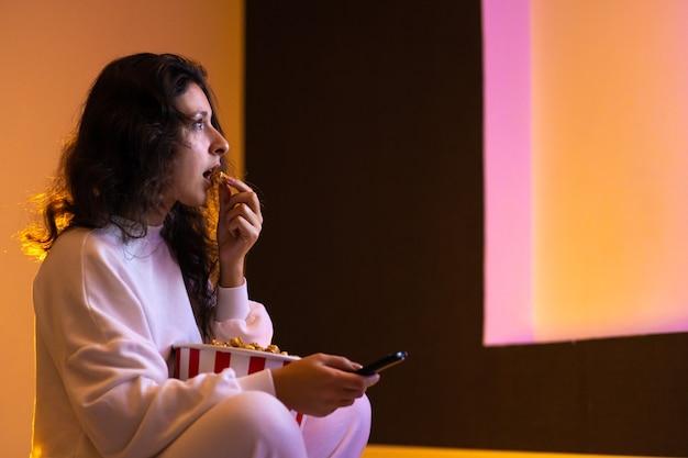 Persoon kijkt naar een film zittend op de bank met een emmer popcorn. Premium Foto