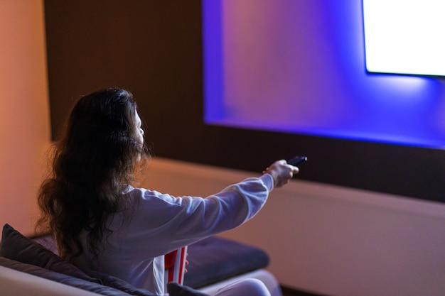 Persoon kijkt naar een film zittend op de bank met een emmer popcorn.