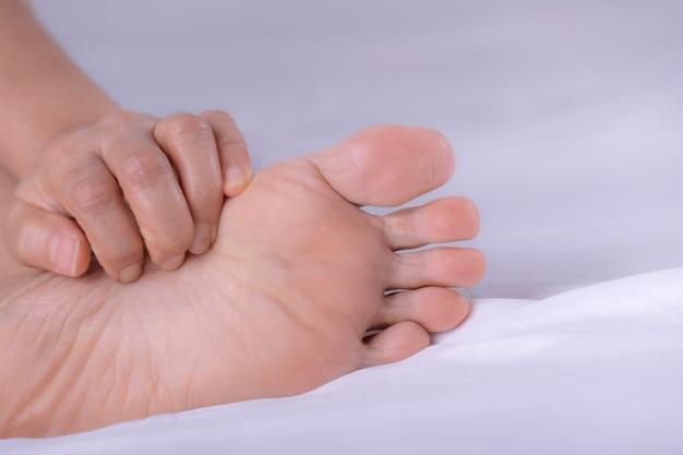 Persoon krabt aan haar voet