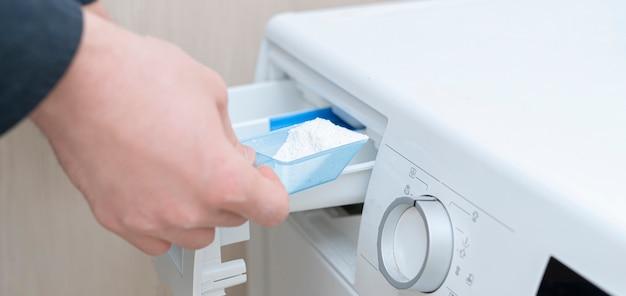 Persoon laadt het waspoeder in de machine