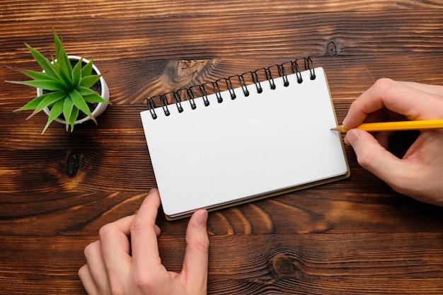 Persoon maakt aantekeningen in een notitieboekje met potlood