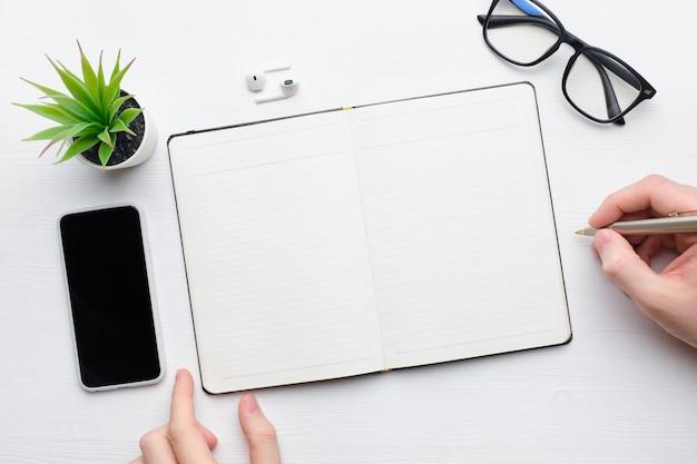 Persoon maakt aantekeningen in het dagboek met de pen