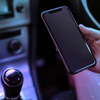 Persoon met behulp van een telefoon in een slimme auto