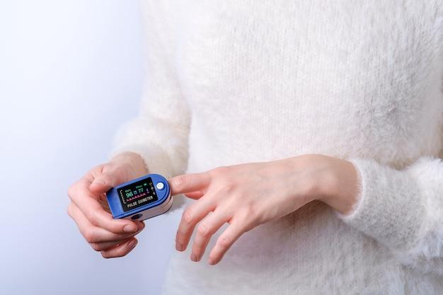 Persoon met behulp van pulsoxymeter apparaat op vinger, gezondheidszorg monitoring concept
