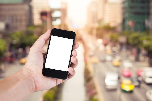Persoon met behulp van smartphone witte scherm houder bij de hand met wazig van verkeersopstopping op de stadsstraat in bangkok thailand.
