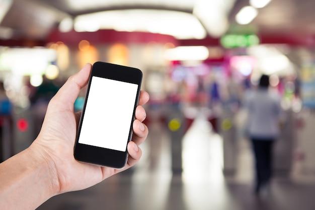 Persoon met behulp van smartphone witte scherm houder bij de hand met wazige achtergrond van mensen die langs ticket machines in elektrische treinstation lopen.