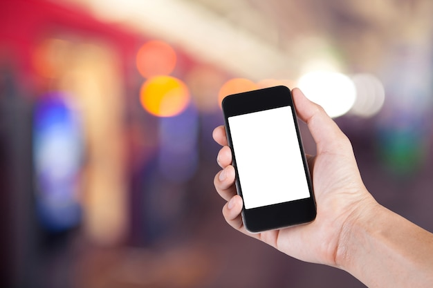 Persoon met behulp van smartphone witte scherm houder bij de hand met wazige achtergrond van mensen lopen in het elektrische treinstation.