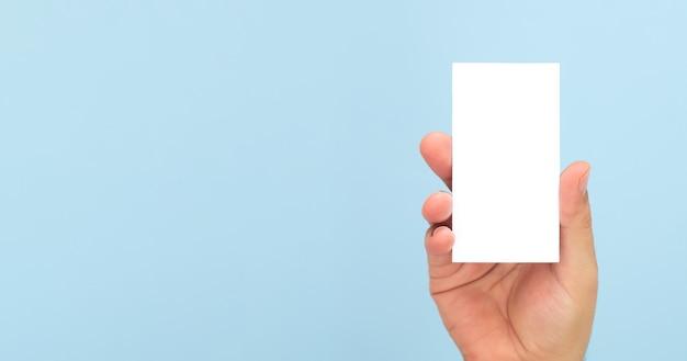 Persoon met blanco visitekaartje op lichtblauwe achtergrond