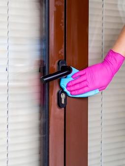 Persoon met chirurgische handschoen schoonmaken deurklink