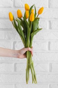 Persoon met een boeket tulpen