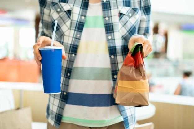 Persoon met een fastfoodpakket en glas met lunch in het openbaar