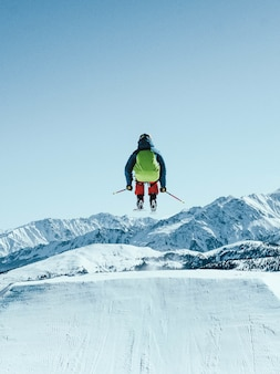 Persoon met een groene rugzak skiën onder de mooie blauwe hemel