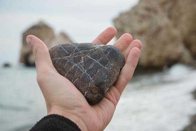 Persoon met een hartvormige rots in zijn handen op het strand