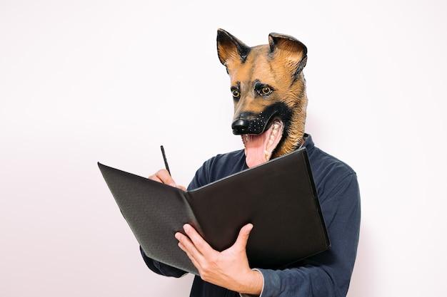 Persoon met een hondenmasker die aantekeningen maakt in een notitieboekje