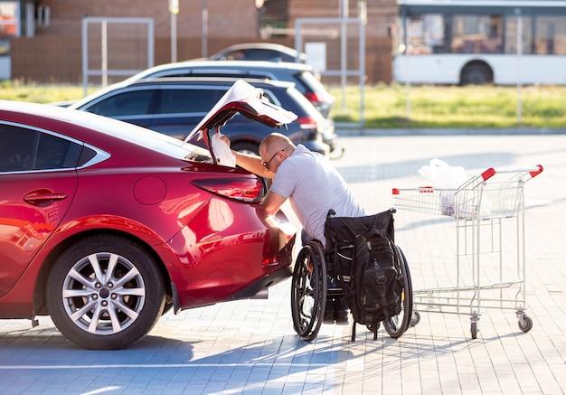 Persoon met een lichamelijke handicap doet aankopen in de kofferbak van een auto op een parkeerplaats van een supermarkt