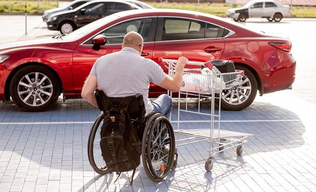 Persoon met een lichamelijke handicap duwt een kar naar een auto op een parkeerplaats van een supermarkt