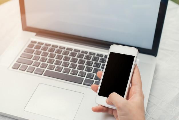 Persoon met een mobiel in de hand en een laptop achter