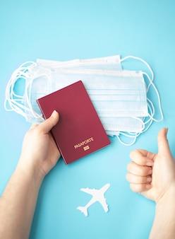 Persoon met een paspoort met chirurgische maskers op een blauwe achtergrond