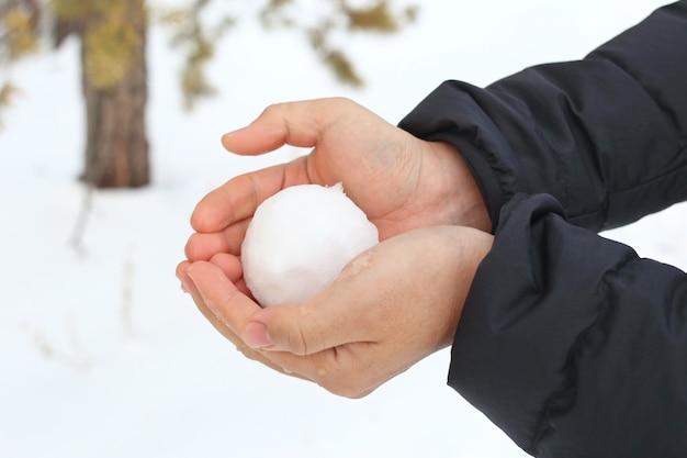 Persoon met een sneeuwbal buitenshuis