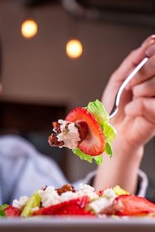 Persoon met een vork die een deel van de salade van groenten en fruit vasthoudt