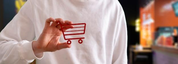 Persoon met een winkelwagentje icoon concept van online winkelen markt verkoop en aankoop