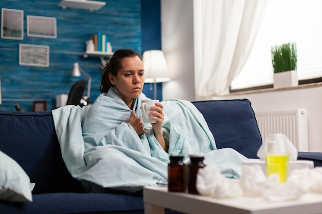 Persoon met een ziekte die thuis wordt behandeld voor verkoudheid en griep zittend op de bank. seizoenssymptomen en hoesten, mok vasthouden met thee of medicijnziektebehandeling. keelziekte gezondheidszorg