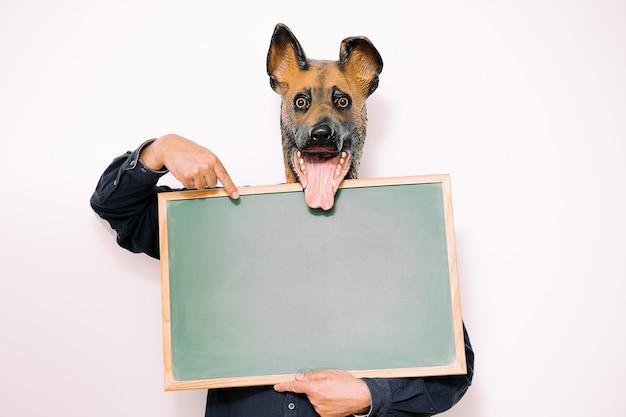 Persoon met gelukkig hondenmasker wijst naar een leeg bord