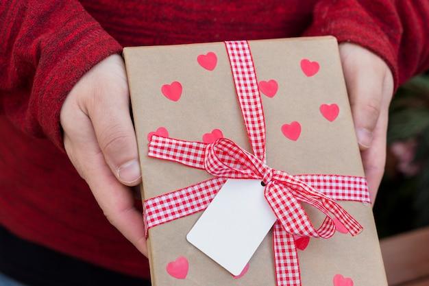 Persoon met geschenkdoos met harten in handen