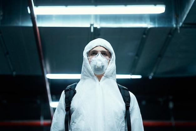 Persoon met gezichtsmasker die beschermende uitrusting tegen een biologisch gevaar draagt