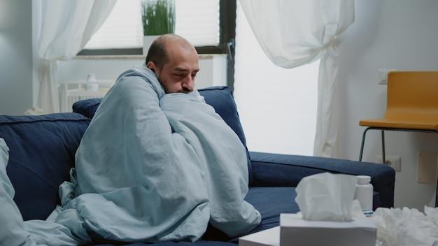 Persoon met griep die het koud heeft en bibbert, gewikkeld in een deken