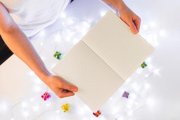 Persoon met het schrijven van boek in de buurt van geschenken en lichtjes van de fee