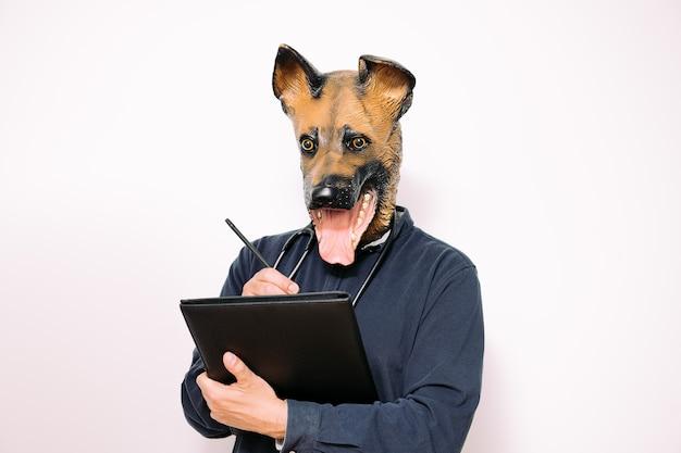 Persoon met hondenmasker die aantekeningen maakt in een map